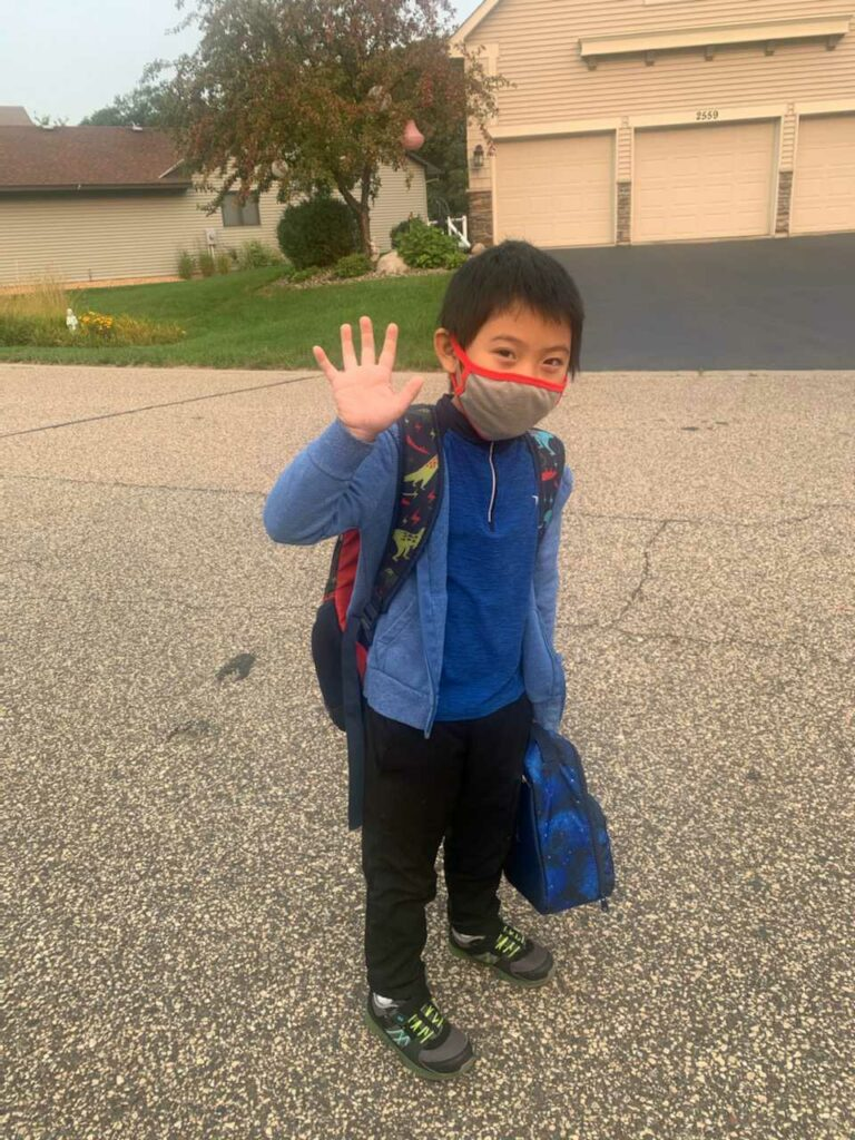 A photo of author LyLy's brother Leland, age 7,standing on a street in front of a house. Leland is wearing a blue jacket and a face mask, and waving at the camera.