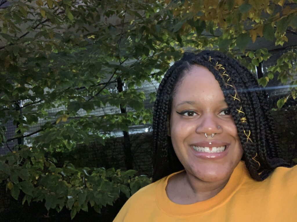 Cierra Brown smiles at the camera in an outdoor setting. She's wearing a yellow shirt. Sunshine filters through trees in the background.