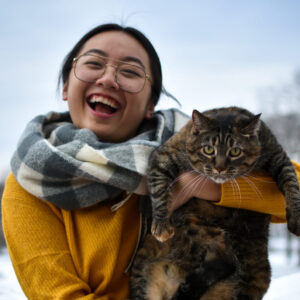 LyLy Vang-Yang holds her cat Bella up and laughs at the camera. Behind them is the blue sky and