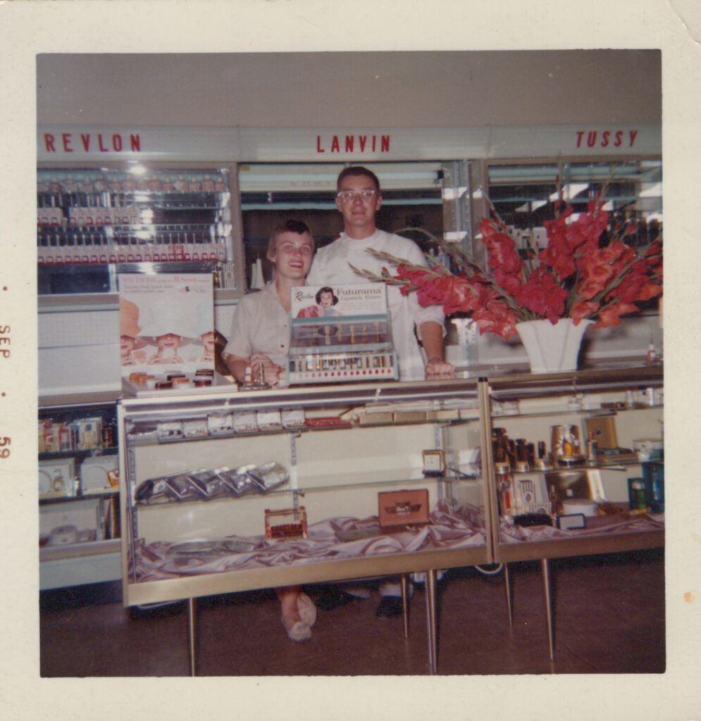 A 1959 photograph of Laura's grandparents, Mary Aspenes (left) and Donald Aspenes at College Pharmacy. The couple smiles at the camera from behind the cosmetics display.