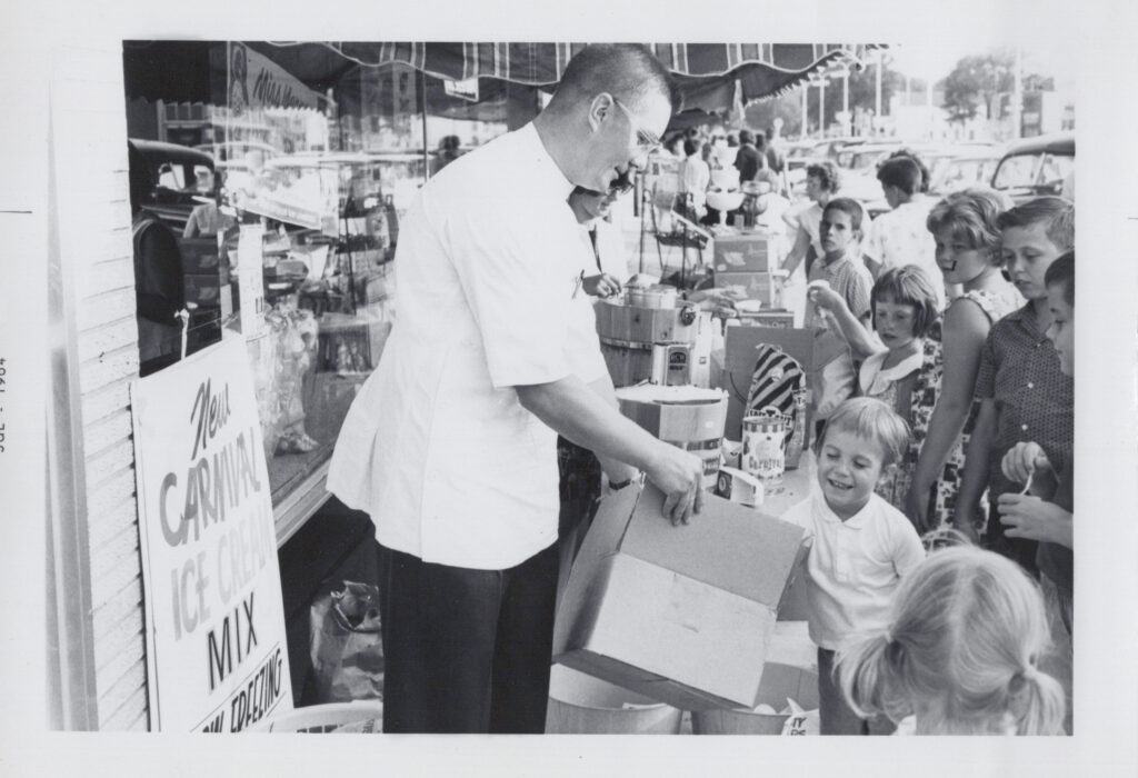 A black and white photograph of Laura's grandpa, Donald Aspenes, handing out treats the local children outside his pharmacy.