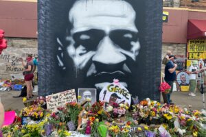 Photo: Black and white mural of George Floyd's face at 38th & Chicago (George Floyd Square). Gifts and flowers from visitors to the memorial cover the ground surrounding the mural.