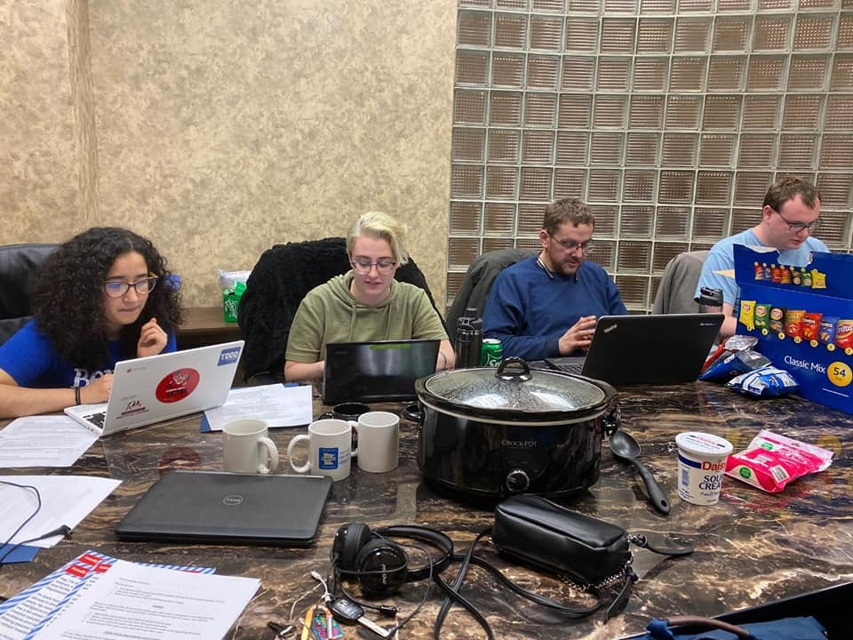 Photo of four people seated around a table, working on laptops and phones.