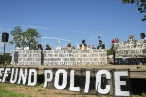 Nine Minneapolis City Council members declared their commitment to defunding and dismantling the Minneapolis Police Department in June 2020, along with the community groups Black Visions and Reclaim The Block.